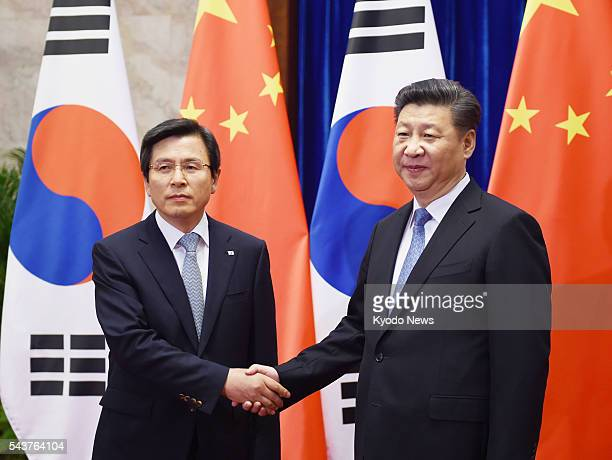 Chinese President Xi Jinping shakes hands with South Korean Prime Minister Hwang Kyo Ahn at the Great Hall of the People in Beijing on June 29 2016...