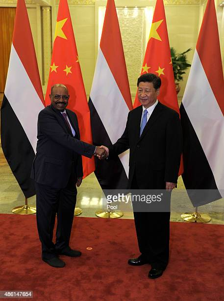 Chinese President Xi Jinping , shakes hands with Sudanese President Omar al-Bashir before their meeting at the Great Hall of the People on September...