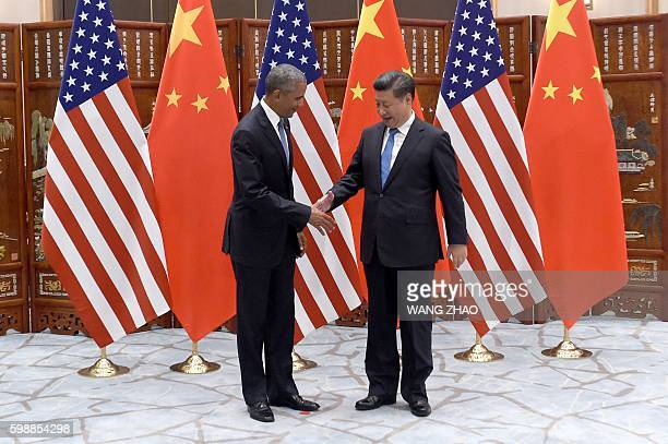 Chinese President Xi Jinping shakes hands with US President Barack Obama before their meeting at the West Lake State Guest House in Hangzhou on...