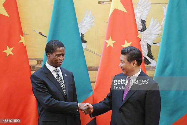 Chinese President Xi Jinping shakes with Zambia's President Edgar Chagwa Lungu during a signing ceremony at the Great Hall of the People on March 30...