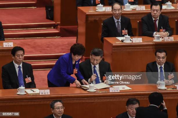 Chinese President Xi Jinping signs a document during the seventh plenary session of the 13th National People's Congress at the Great Hall of the...