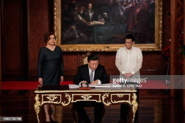 Chinese President Xi Jinping signs the guest book as Philippines' President Rodrigo Duterte and his daughter Sarah Duterte look on at the Malacanang...