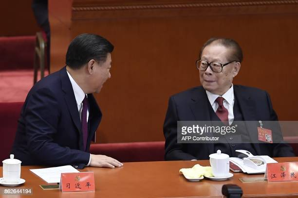 Chinese President Xi Jinping speaks to China's former president Jiang Zemin at the opening session of the Chinese Communist Party's Congress at the...