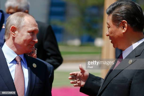 Chinese President Xi Jinping speaks with Russian President Vladimir Putin as delegation heads arrive for a family photo during the Belt and Road...