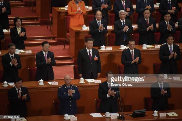 Chinese President Xi Jinping stands still after after hearing the results of his elected for a second fiveyear term during the 5th plenary session of...
