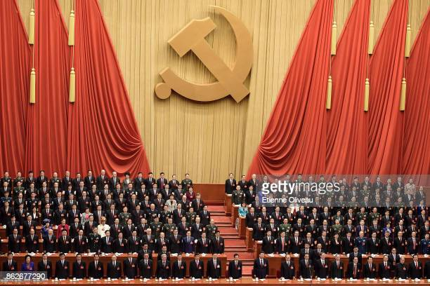 Chinese President Xi Jinping stands up to listen to the National Anthem among other members of the Communist Party Of China during the opening...