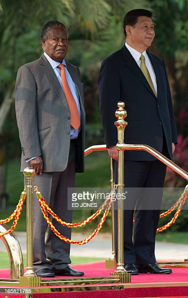 Chinese President Xi Jinping stands with Zambia's President Michael Sata during a welcoming ceremony in Sanya on the southern Chinese resort island...