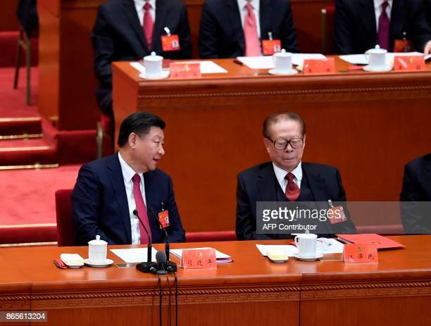 Chinese President Xi Jinping talks to China's former president Jiang Zemin during the closing of the 19th Communist Party Congress at the Great Hall...