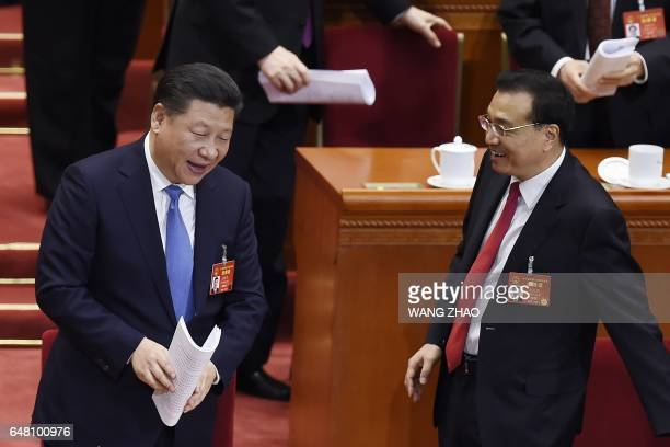 Chinese President Xi Jinping talks with Chinese Premier Li Keqiang during the opening session of the National People's Congress, China's legislature,...