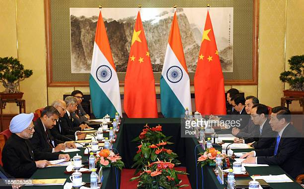 Chinese President Xi Jinping talks with India's Prime Minister Manmohan Singh during a meeting at the Diaoyutai State Guesthouse on October 23 2013...
