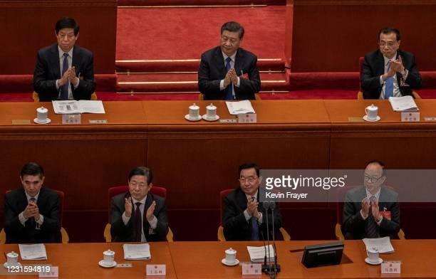 Chinese President Xi Jinping, top center, Premier Li Keqiang, right, and NPC Chairman Li Zhanshu applaud during a speech at the second plenary...