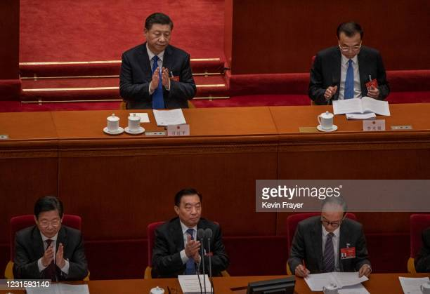 Chinese President Xi Jinping, top left, and Premier Li Keqiang applaud during a speech by NPC Chairman Li Zhanshu at the second plenary session of...