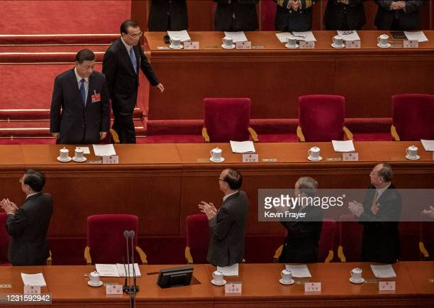 Chinese President Xi Jinping, top left, and Premier Li Keqiang, top right, arrive at the second plenary session of the National People's Congress at...