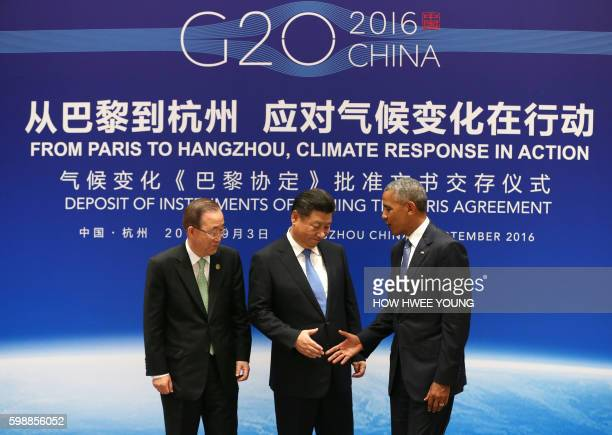 TOPSHOT Chinese President Xi Jinping US President Barack Obama and UN Secretary General Ban Kimoon shake hands during a joint ratification of the...