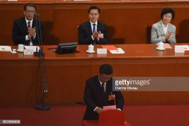 Chinese President Xi Jinping votes during his election for a second fiveyear term during the 5th plenary session of the first session of the 13th...