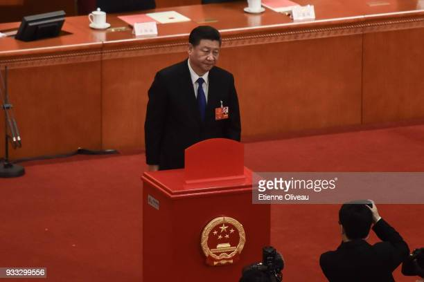 Chinese President Xi Jinping votes during the sixth plenary session of the National People's Congress at the Great Hall of the People on March 18...