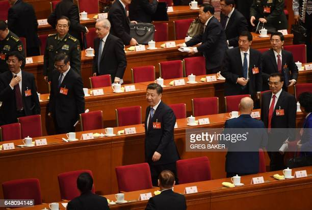 Chinese President Xi Jinping walks out at the end of the opening session of the National People's Congress, China's legislature, in the Great Hall of...