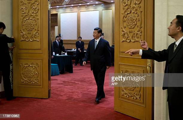 Chinese President Xi Jinping walks out of a meeting room to shake hands with visiting Swiss Federal President Ueli Maurer while security guards...