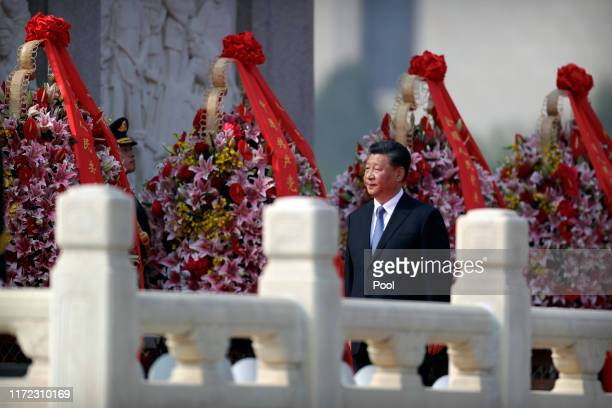 Chinese President Xi Jinping walks past floral wreaths at the Monument to the People's Heroes during a ceremony to mark Martyr's Day at Tiananmen...