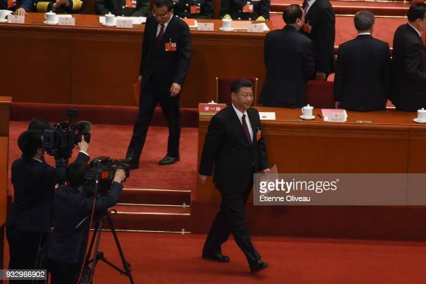 Chinese President Xi Jinping walks with a ballot hin his hand during his election for a second fiveyear term during the 5th plenary session of the...