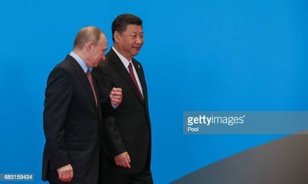 Chinese President Xi Jinping walks with Russian President Vladimir Putin as they attend the welcome ceremony at Yanqi Lake during the Belt and Road...