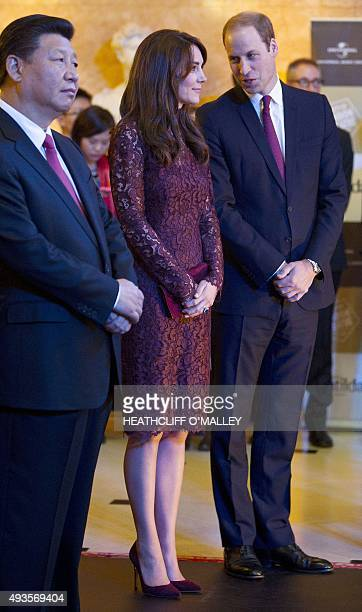 Chinese President Xi Jinping watches a performance as Britain's Prince William Duke of Cambridge talks to his wife Britain's Catherine Duchess of...