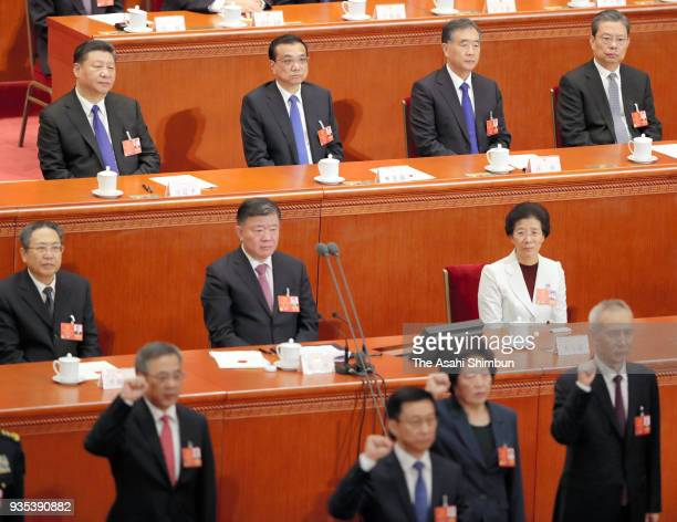 Chinese President Xi Jinping watches delegation swearing an oath during the seventh plenary session of the 13th National People's Congress at the...