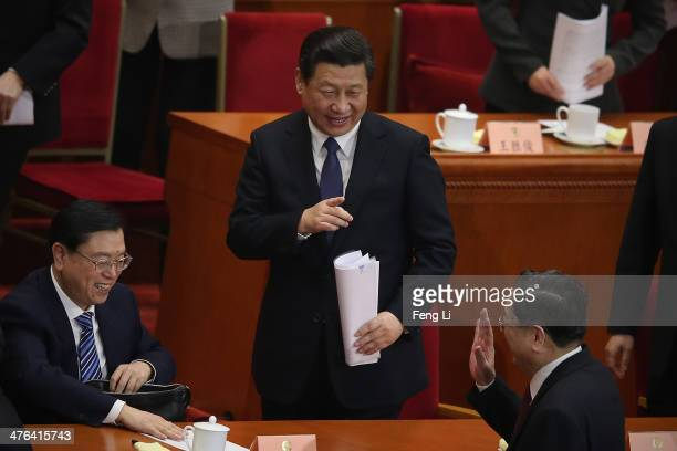 Chinese President Xi Jinping waves to Chairman of the Chinese People's Political Consultative Conference Yu Zhengsheng after the opening of the 2nd...