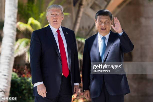 TOPSHOT Chinese President Xi Jinping waves to the press as he walks with US President Donald Trump at the MaraLago estate in West Palm Beach Florida...