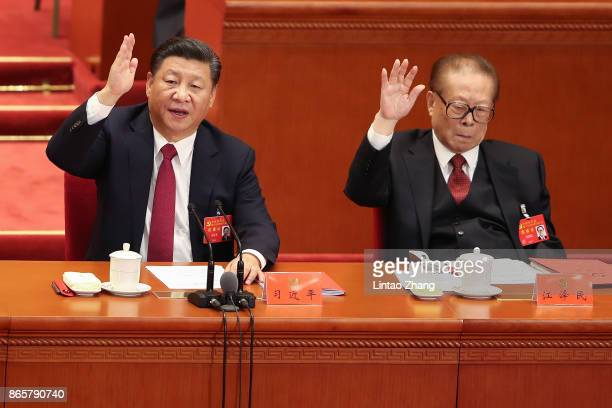 Chinese President Xi Jinping with China's former president Jiang Zemin vote at the closing of the 19th Communist Party Congress at the Great Hall of...