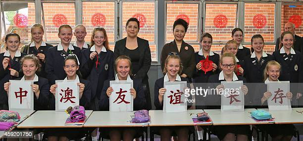Chinese President Xi Jinpin's wife Madame Peng Liyuan poses for a photo with students during their lessons in Mandarin calligraphy papercutting and...