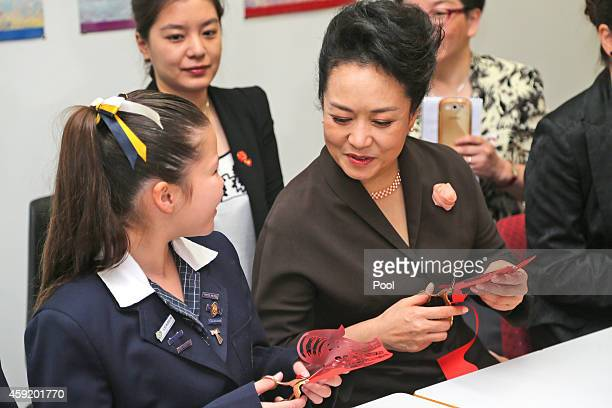 Chinese President Xi Jinpin's wife Madame Peng Liyuan sits with students during their lessons in Mandarin calligraphy papercutting and embroidery at...