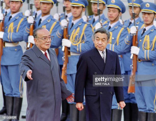 Chinese President Yang Shangkun and Japanese Emperor Akihito review the honor guard in front of the Great Hall of the People in Beijing 23 October...