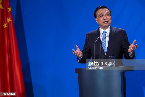 Chinese Prime Minister Li Keqiang gestures at a press conference with German Chancellor Angela Merkel at the Chancellery on May 26 2013 in Berlin...