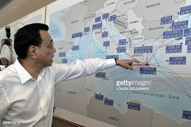 Chinese Prime Minister Li Keqiang looks at a shipping routes map at the port of Piraeus where Chinese shipping giant Cosco controls two of the three...