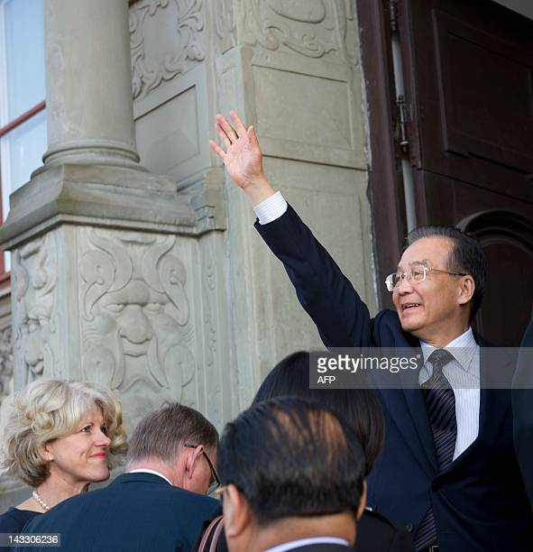Chinese Prime Minister Wen Jiabao waves upon arrival at the governor's residence in Goteborg on April 23 2012 as Governor Lars Backstrom and his wife...