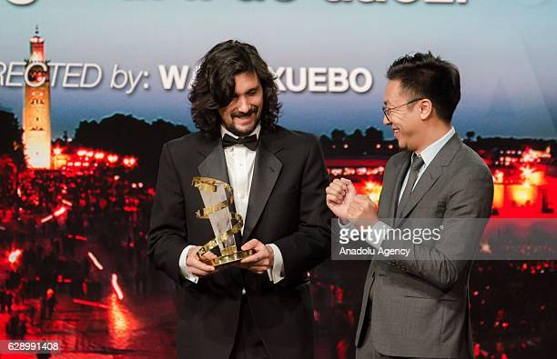 Chinese producer Wang Zijian receives the best directing prize for the film Knife in the Clear Water from Lisandro Alonso during the closing ceremony...
