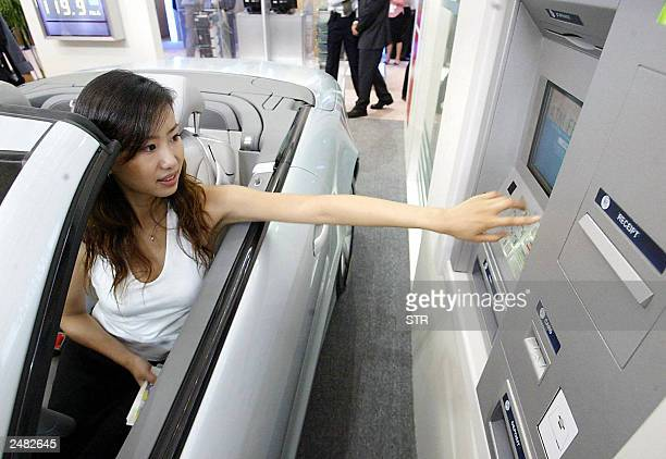 A Chinese promoter shows off the latest driveby automated teller machine on display at a banking exhibition in Beijing 07 September 2003 China is...