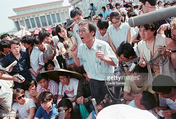 A Chinese protester uses a microphone to address the crowd at Tiananmen Square Several journalists are in the crowd with tape recorders