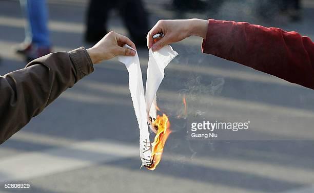 Chinese protesters burn a Japanese flag outside the Japanese Embassy during an antiJapanese demonstration on April 9 2005 in Beijing China Up 10000...