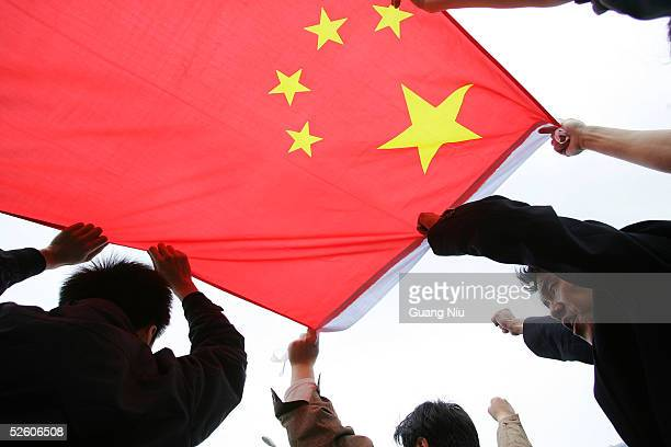 Chinese protesters carry the national flag as they march during an antiJapanese demonstration on April 9 2005 in Beijing China Several thousand...