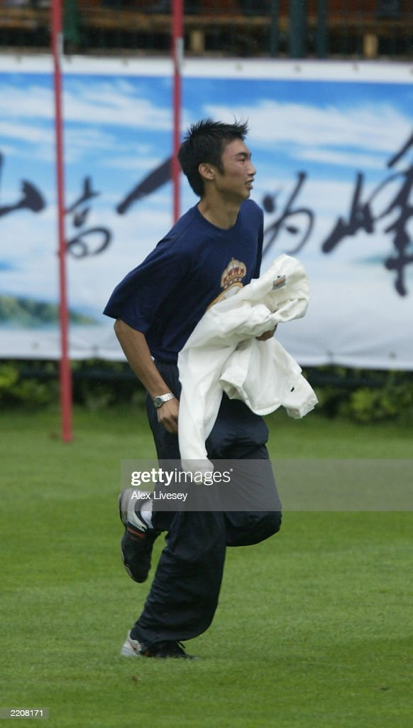 A Chinese Real madrid fan breaks through security and tries to reach David Beckham during a training session at the Hongta Sports Centre on July 26, 2003 in Kunming, China.