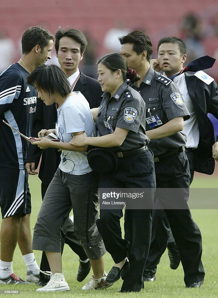 A chinese Real Madrid fan is dragged off the pitch by security after running on to get an autograph from thw players during a training session on August 1, 2003 at the Workers Stadium in Beijing, China.