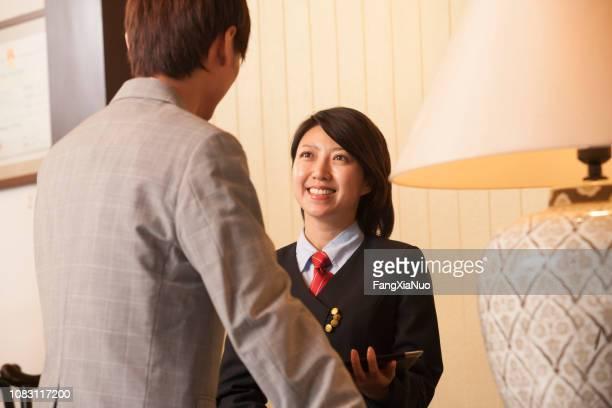ホテルのロビーでクライアントと中国の受付 - ホテルマン ストックフォトと画像