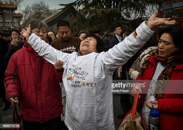 Chinese relative of a missing passenger on Malaysia Airlines flight MH370 reacts as she weeps outside the main gate of the Lama Temple on March 8,...