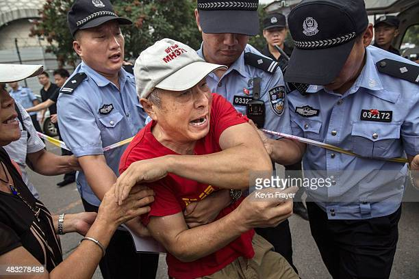 Chinese relative of a passenger missing on Malaysian Airlines flight MH370 scuffles with police after trying to break through a barricade to reach...