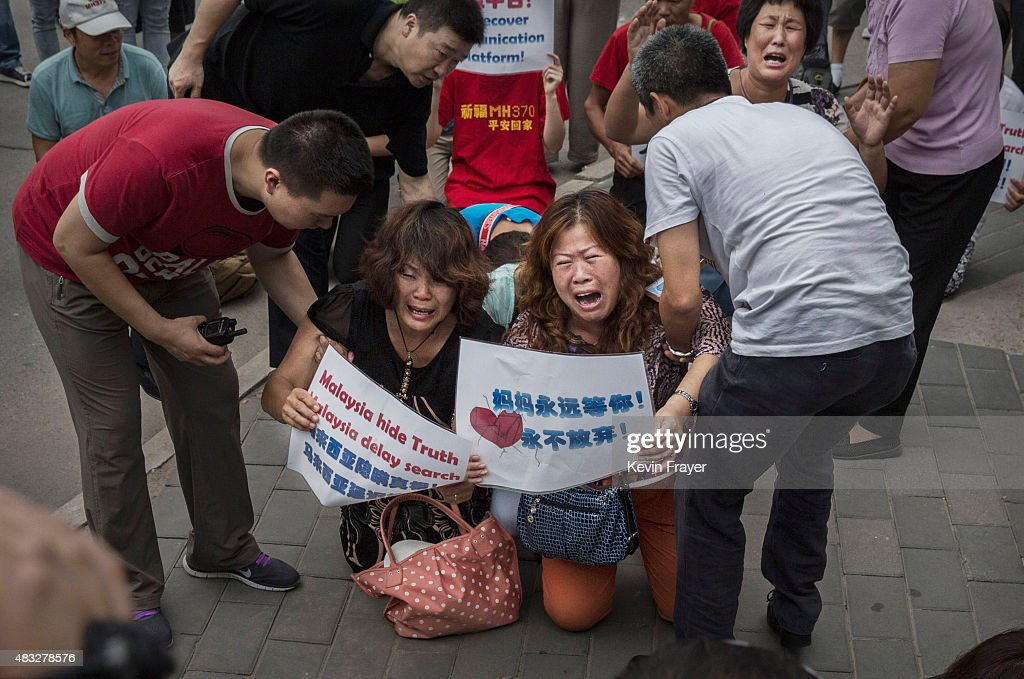 Chinese relatives of passengers missing on Malaysian Airlines flight MH370 cry as they kneel in front of the media outside the Malaysian Embassy during a protest by relatives on August 7, 2015 in Beijing, China. Today, France expanded its search for debris off Reunion Island, a day after Malaysia's prime minister announced that the piece of wing discovered last week is from Malaysia Airlines Flight MH 370, which vanished last year. Officials and experts from other countries, including the United States and Australia, have been more cautious, saying that more investigating needs to be done.