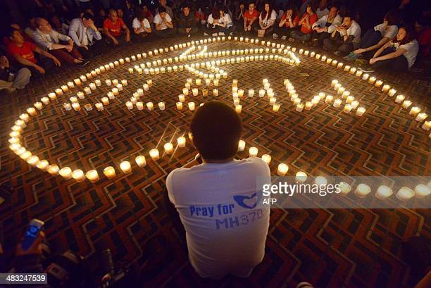 Chinese relatives of passengers on the missing Malaysia Airlines flight MH370 take part in a prayer service at the Metro Park Hotel in Beijing on...
