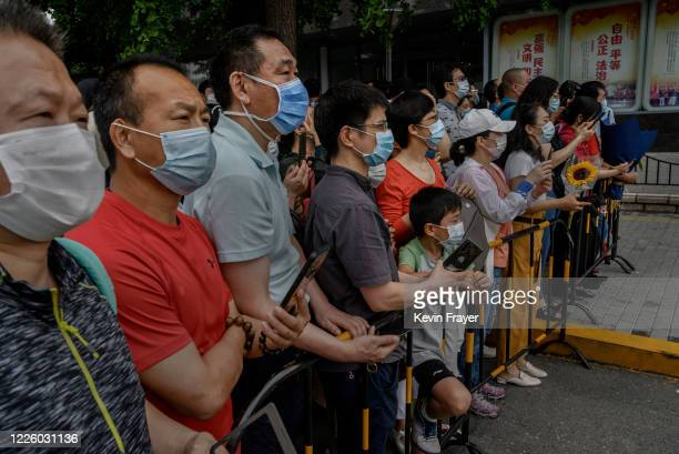 Chinese relatives stand behind a fence as they wait for students to come out of the school on the final day of the National College Entrance...
