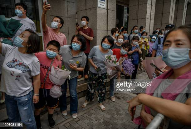 Chinese relatives take photos and hold flowers as they wait for students to come out of the school on the final day of the National College Entrance...